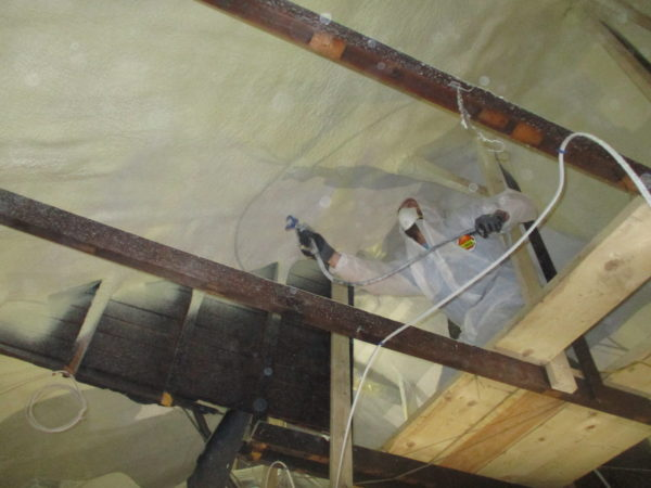 Intumescent fire barrier coating applied over closed cell spray foam.
